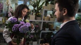 Gullig blomsterhandlare som råder köparen som växer den inlagda blomman stock video