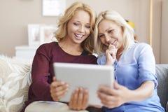 Gullig blond flicka som använder minnestavlan med mamman Arkivfoto