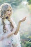 Gullig blond kvinna i den tropiska trädgården arkivfoto