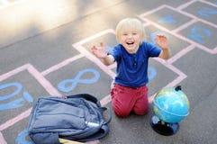 Gullig blond pojke som hoppar hage leken efter skola med påsar som nära lägger Arkivbilder