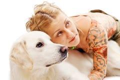 Gullig blondin som kramar en retriever Fotografering för Bildbyråer