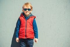 Gullig blondy pojke i en modern outerwear, utomhus royaltyfri foto