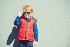 Gullig blondy pojke i en modern outerwear, utomhus arkivbilder