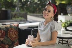 Gullig brunett i röd bandana och gråa utslagsplatsen som sitter i utomhus- kafé med drinken royaltyfria foton