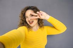Gullig brunett plus formatkvinna med lockigt hår i gul tröja royaltyfria bilder