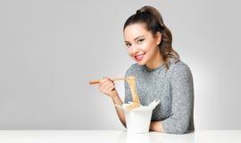 Gullig brunett som äter asiatisk mat Arkivfoto