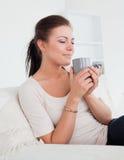 Gullig brunett som tycker om en kopp av tea Arkivfoton