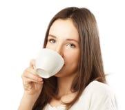 Gullig brunettflicka som dricker kaffe royaltyfri fotografi