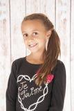 Gullig brunnetteflicka med ett trevligt leende i svartöverkant Royaltyfri Bild