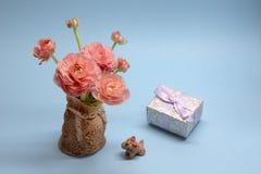 Gullig bukett av mjuka rosa sm?rblommor och en g?va p? en bl? bakgrund royaltyfri bild