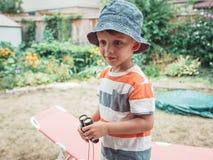 gullig Caucasian pojke i avriven tshirt och hatten som ser till och med kikare arkivbild