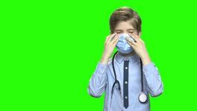 Gullig caucasian pojke som spelar doktorn arkivfilmer