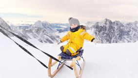 Gullig caucasian pys som sledding i fjällängberg fotografering för bildbyråer