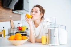 Gullig charmig kvinnadanandefruktsaft och ätaapelsiner Royaltyfri Fotografi
