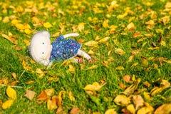 Gullig docka som ligger på gräset Royaltyfri Foto