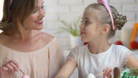 Gullig dotter som kysser modern på kind som dekorerar påskägg som förbereder sig för fest stock video