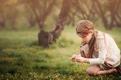 Gullig drömlik ungeflicka i beigea dräktplockningblommor i vårträdgård arkivbilder