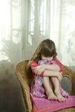 gullig drömma flicka little som sitter arkivfoto