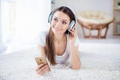 Gullig drömma ung flicka som lyssnar till musik, i att ligga för hörlurar royaltyfri fotografi