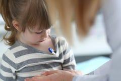 Gullig eftert?nksam liten flicka med termometern under hennes armh?la royaltyfri foto