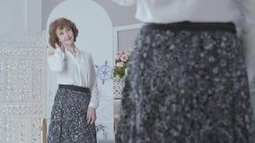 Gullig elegant äldre kvinna som ser i spegeln som undersöker hennes reflexion Damen som ser hennes nya långa kjol i arkivfilmer