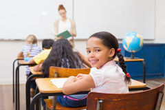 Gullig elev som ler på kameran i klassrum Arkivfoto