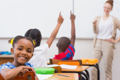 Gullig elev som ler på kameran i klassrum Royaltyfri Foto