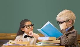 Gullig elevuppklädd som lärare i klassrum Arkivbild