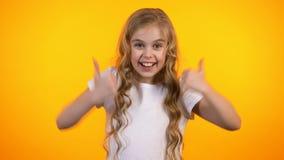 Gullig emotionell skolflicka som visar tummar-upp, extremt tillfredsställt barn, promo lager videofilmer