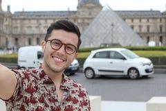Gullig etnisk man som utomhus tar en selfie royaltyfri fotografi