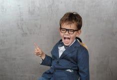 Gullig europeisk pojke i ett omslag med punkter för en fjäril hans finger på väggen royaltyfria bilder