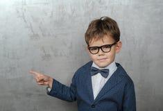 Gullig europeisk pojke i ett omslag med punkter för en fjäril hans finger på väggen arkivbild