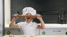 Gullig förskole- pojke i aprin- och shefhatten som spelar med en kavel som har gyckel Matlagning är rolig 4 K stock video