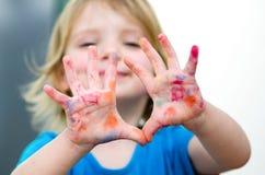 Gullig förskolebarnflicka med färgade händer för leende visning Selectiv Royaltyfria Foton