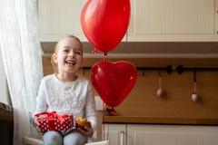 Gullig förskolebarnflicka som firar den 6th födelsedagen Flicka som rymmer hennes födelsedagmuffin och beautifully slågna in gåva Arkivfoto