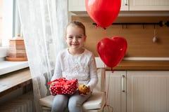 Gullig förskolebarnflicka som firar den 6th födelsedagen Flicka som rymmer hennes födelsedagmuffin och beautifully slågna in gåva Arkivbilder