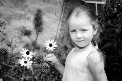 Gullig förskolebarnflickastående med naturliga blommor Royaltyfri Fotografi