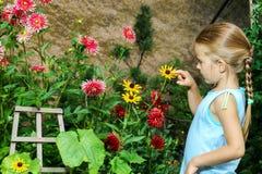 Gullig förskolebarnflickastående med naturliga blommor Royaltyfria Bilder