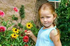 Gullig förskolebarnflickastående med naturliga blommor Fotografering för Bildbyråer