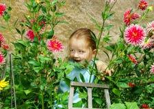 Gullig förskolebarnflickastående med naturliga blommor Arkivfoton