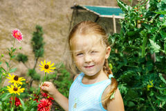 Gullig förskolebarnflickastående med naturliga blommor Arkivbild