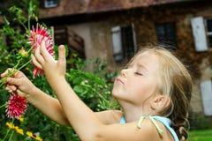 Gullig förskolebarnflickastående med naturliga blommor Arkivbilder