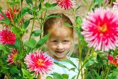 Gullig förskolebarnflickastående med naturliga blommor Arkivfoto