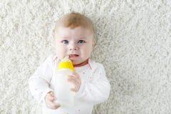 Gullig förtjusande ewborn behandla som ett barn den hållande sjukvårdflaskan för flickan, och dricka formel mjölka Royaltyfri Bild