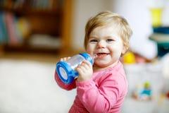 Gullig förtjusande ewborn behandla som ett barn den hållande sjukvårdflaskan för flickan, och dricka formel mjölka eller bevattna Arkivfoton