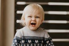 Gullig förtjusande liten blond litet barnunge som skrattar, har gyckel och gör enfaldiga framsidor utanför hemmastatt på den utep royaltyfri bild