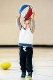Gullig förtjusande liten liten vit Caucasian barnlitet barnpojke som spelar med bollbasket i idrottshall på vanlig bakgrund för v Arkivbild