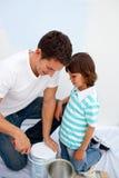 gullig fader för pojke hans små målningslokal royaltyfria bilder