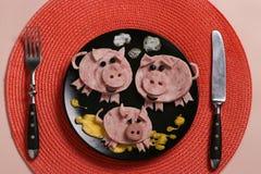 Gullig familj av svin - frukost för barn från skinka och omelett, kulinarisk idé royaltyfria foton