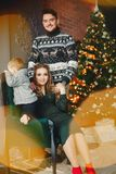 Gullig familj som sitter nära julgranen royaltyfri fotografi